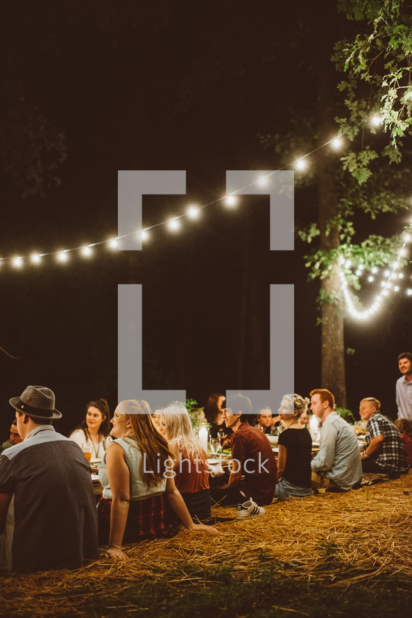Guests sitting at an outdoor table lit by strings of lights.