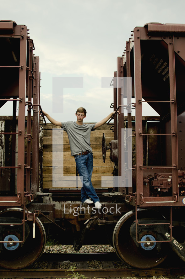 boy standing on hitches between two railroad cars