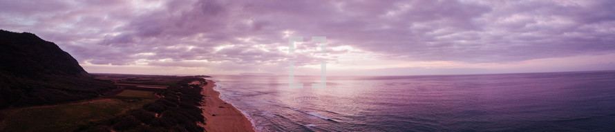 purple sky over the ocean and shoreline
