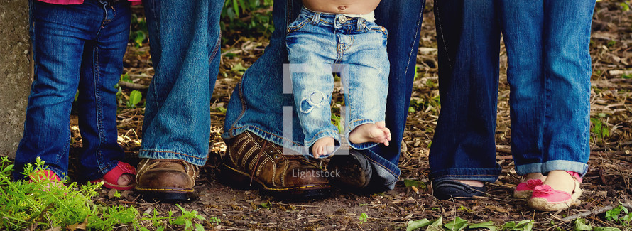 the legs and feet of a family in denim