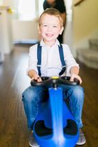 a little boy riding a plasma car in a hallway