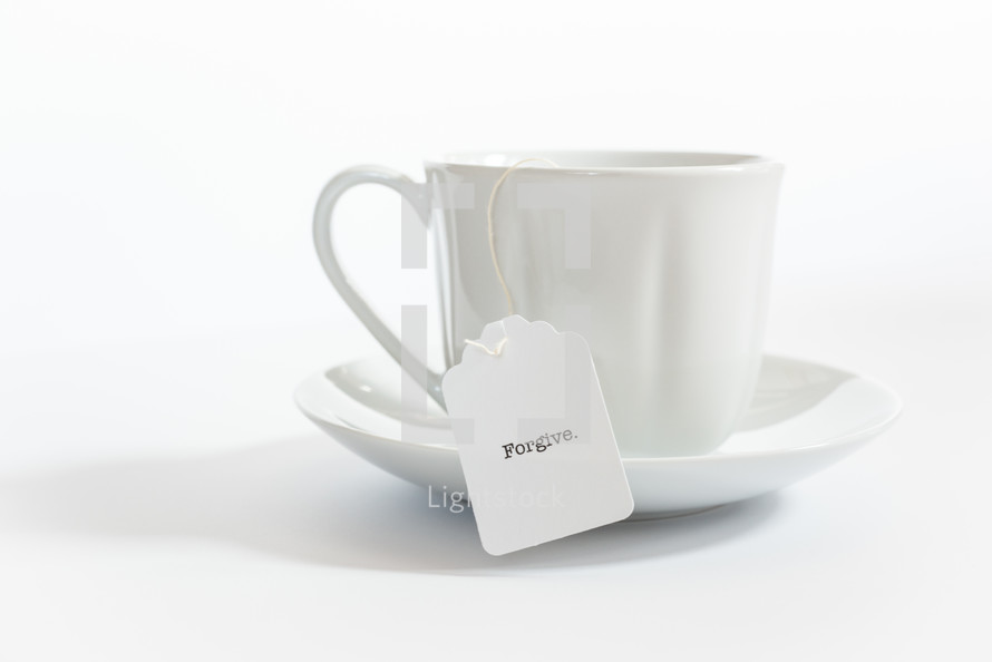 tea cup with the word forgive on the tea bag