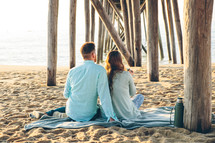 a couple sitting on a blanket under a pier on a beach