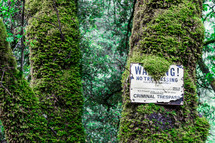 A warning sign partially covered by moss