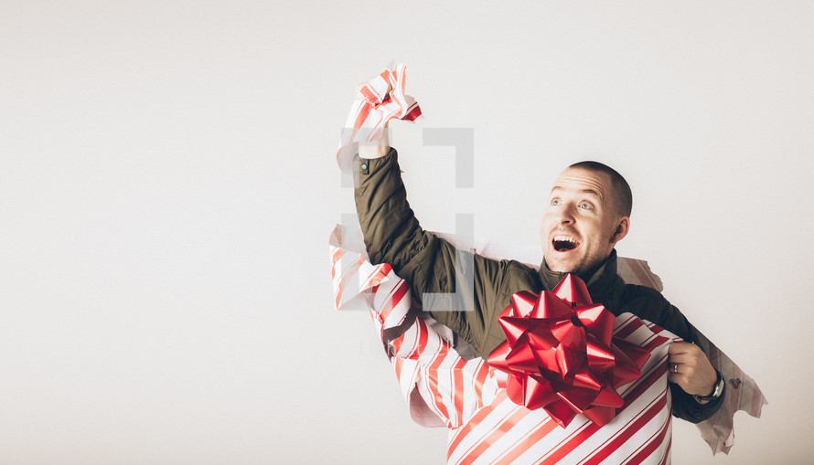 A man breaks free from wrapping paper