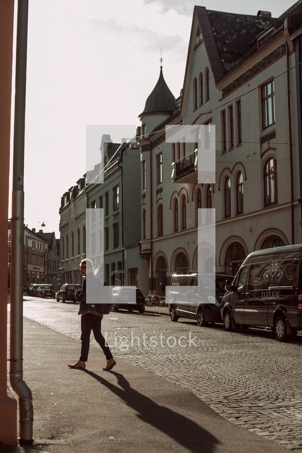 a man walking down a sidewalk along side a cobblestone street
