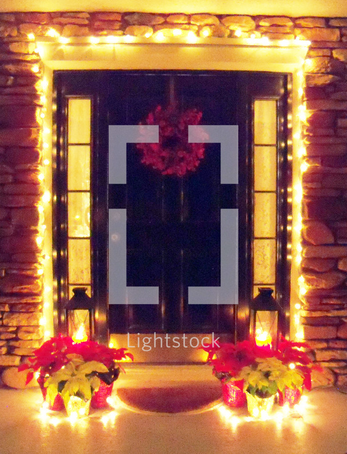 Christmas lights, wreath and poinsettia plants decorate the front door entrance to a home getting ready for family and friends over the holidays to celebrate Christmas time and make a house feel like a home.