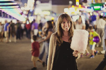 woman holding cotton candy at a fair