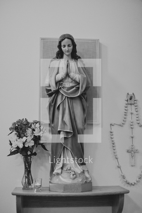 praying Modonna statue and rosary