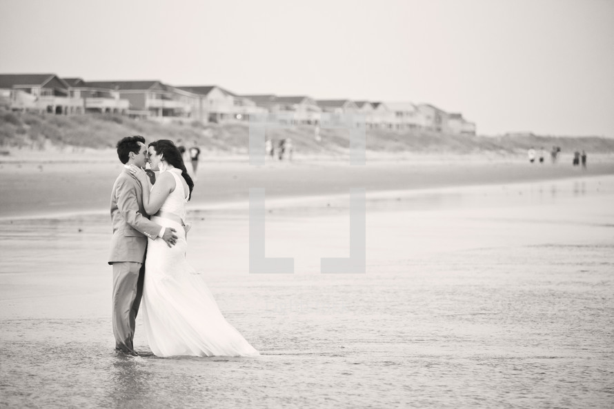 bride and groom kissing on a beach in the water