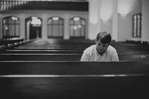 A man sitting in a pew alone in a church sanctuary