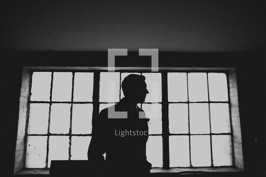 The profile of a groom in front of windows in a warehouse
