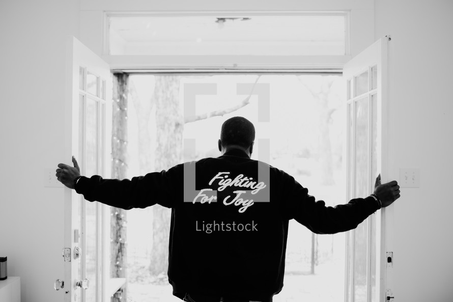 "A man looking out of a doorway, wearing a jacket that reads, ""Fighting For Joy."""