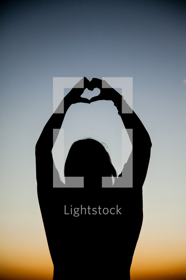 Silhouette of person making a heart shape with their hands with arms extened over head with sunset in background..