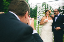 A man taking a picture of a bride and groom.