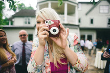 A woman taking a picture with a camera at a wedding reception.