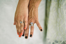 A bride and her mother's hands wearing their wedding rings.