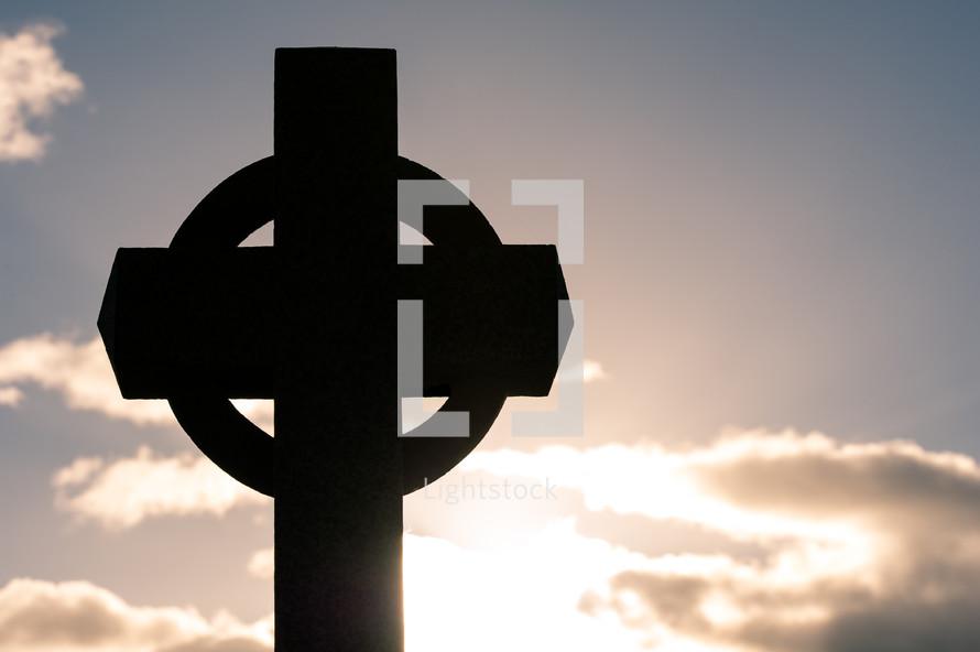 Cross statue with sun and clouds