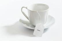 tea cup with the word faith on the tea bag