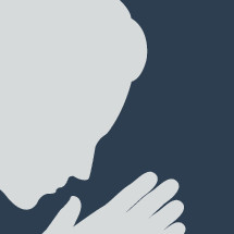 silhouette of a man with head bowed and praying hands