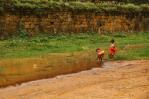 girl's playing in a puddle in Cambodia