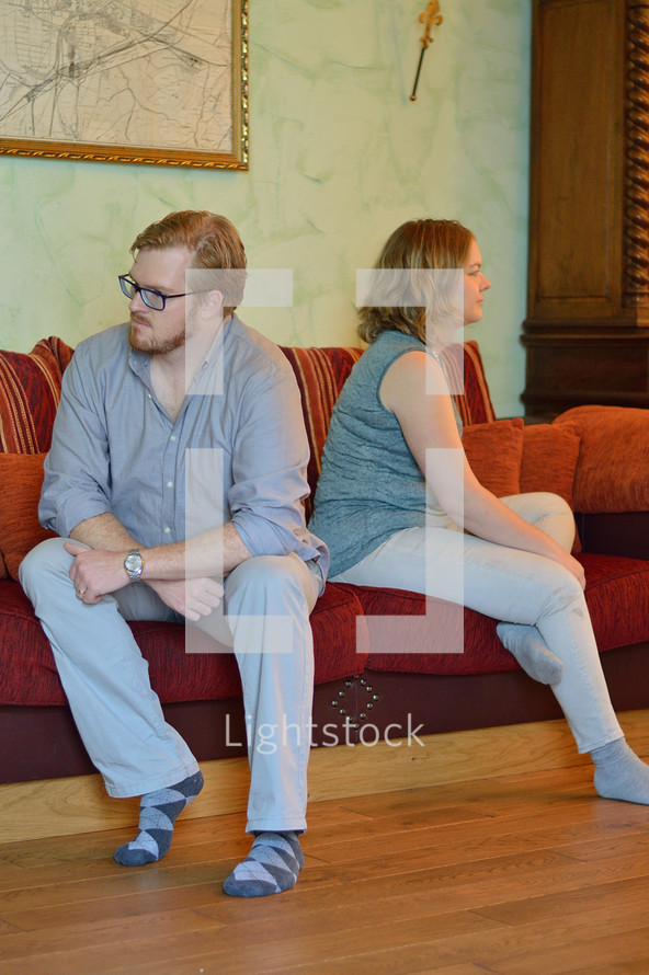 a couple sitting on a couch not speaking to each other
