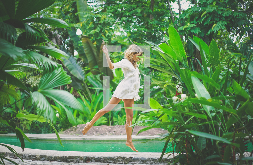 a woman jumping amongst tropical plants