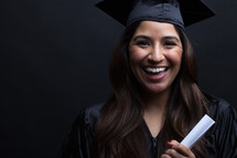 a smiling graduate holding a diploma