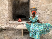 a woman balancing a bowl of fruit on her head