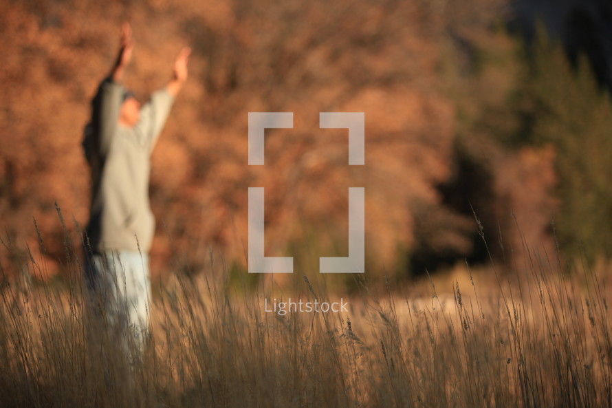 man in a field with arms raised