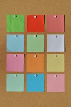 colorful blank notepads on a  corkboard