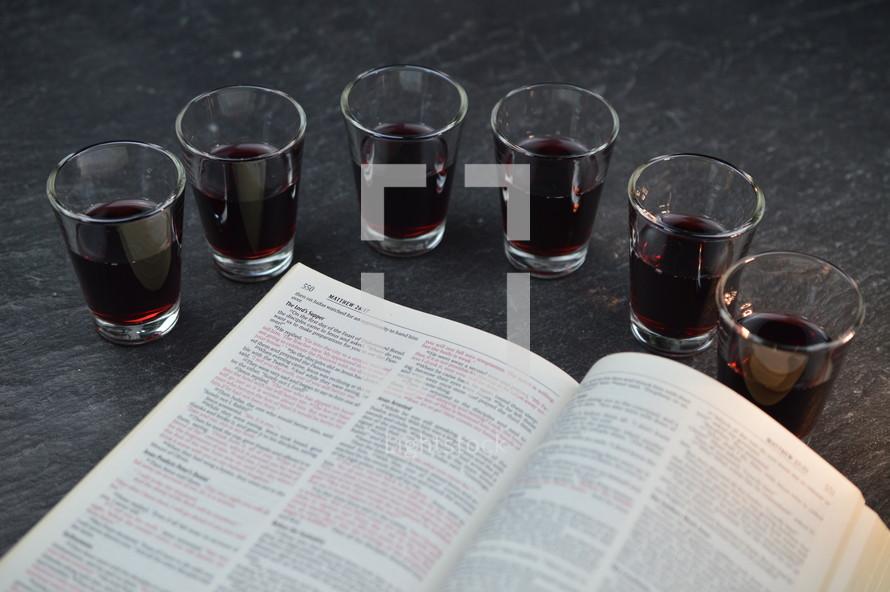 communion wine cups and open Bible