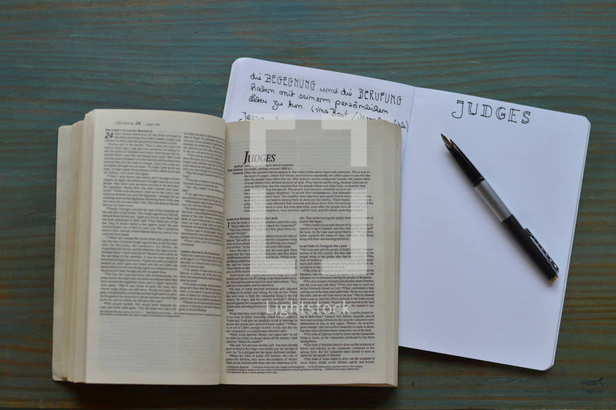 bible studies with a bible open at the book of Judges with notes and pen on a wooden cyan table