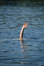 A hand raised out of the water for help.