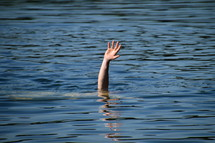 a hand raised out of the water for help