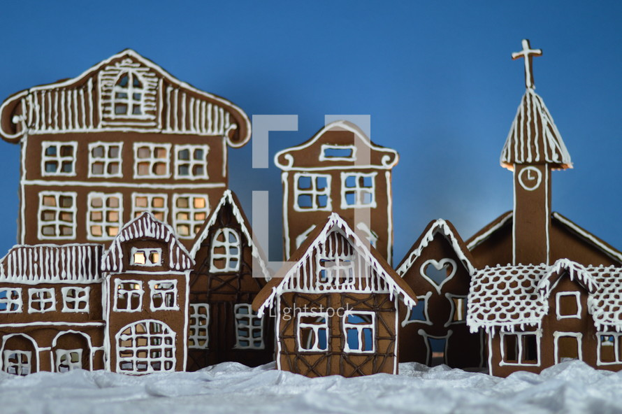 home made gingerbread village in front of blue background on white snowlike velvet as advent decoration