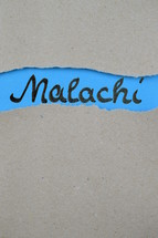 torn open kraft paper over blue paper with the name of the prophetic book Malachi