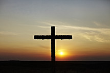 The sun goes down on a cross erected on a hillside.