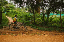 Boy and a bike on a dirt road in Cambodia