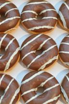 Chocolate covered donuts with white stripes
