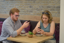 a couple sitting at a table together texting on their phones