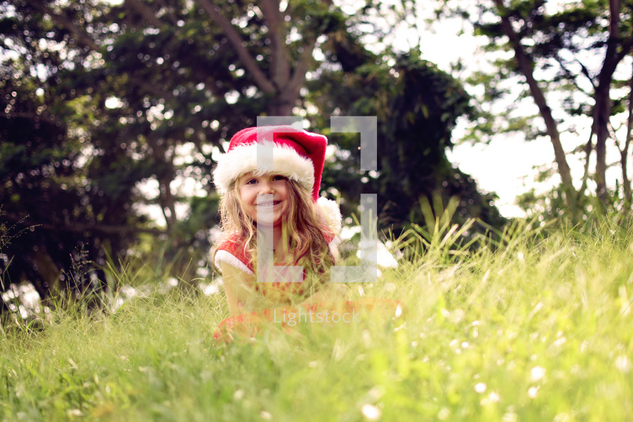 a little girl in a santa hat hiding in the grass