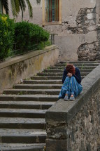 a sad young woman sitting along on concrete steps