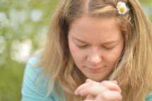 Young blond woman praying outdoors