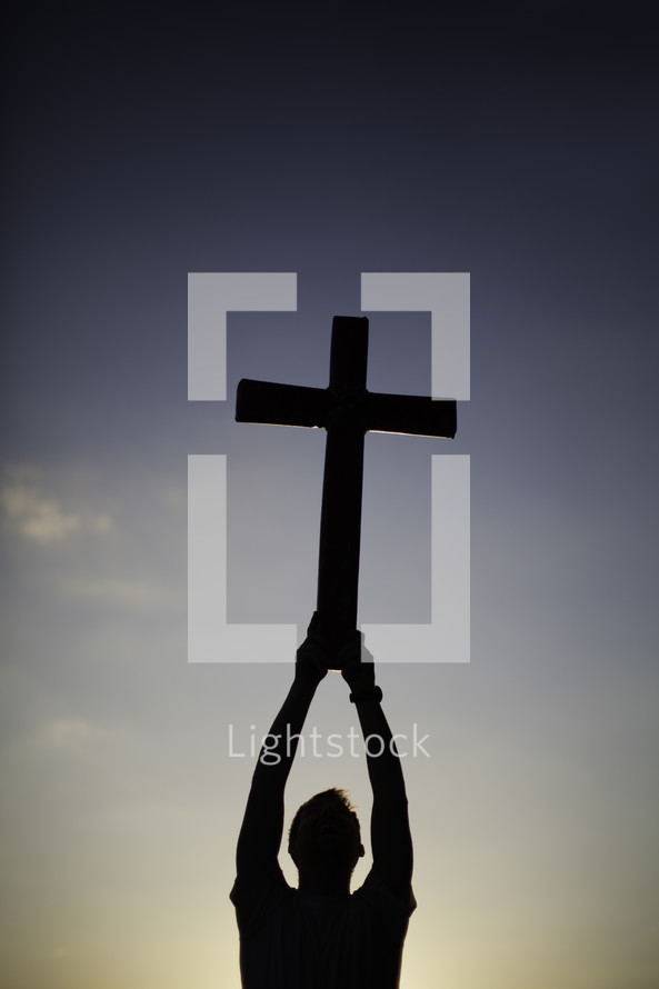 Silhouette of man holding cross over head in the air at dusk.