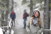 woman standing outdoors in falling snow
