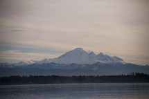 snow capped peaks across a lake