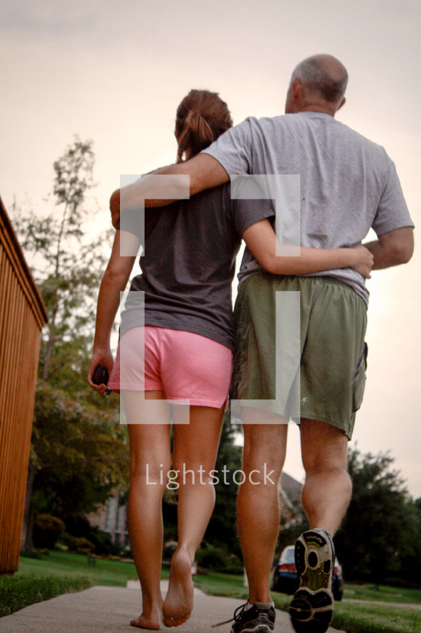 A father and daughter walking down a sidewalk with arms around each other.