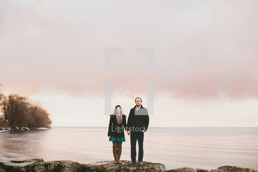 a couple holding hands standing on a rocky shore