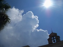 The Heavens roll away like a curtain revealing the glory of God. Clouds covering a bell tower on a sunny day.